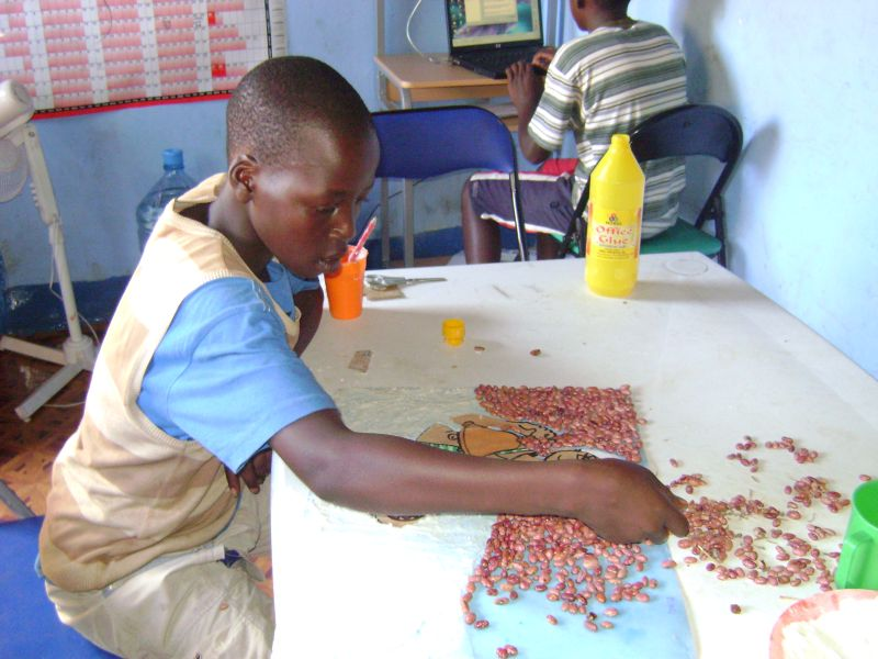 A young Ugandan helps slum kids use computers and have nutritious school meals